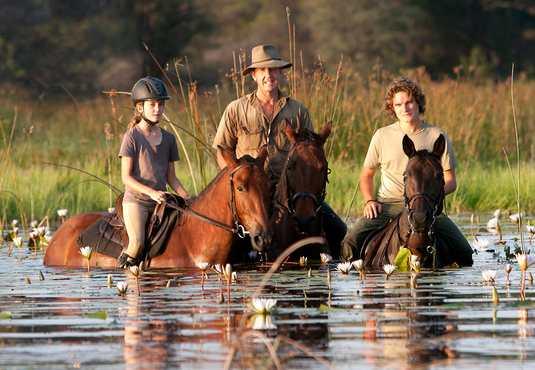 Foot family riding across the Thamalakane River, Botswana