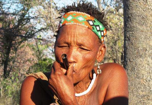 Bushmen woman smoking pipe