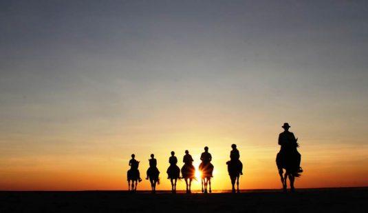 Horse riders in the Makgadikgadi sunset