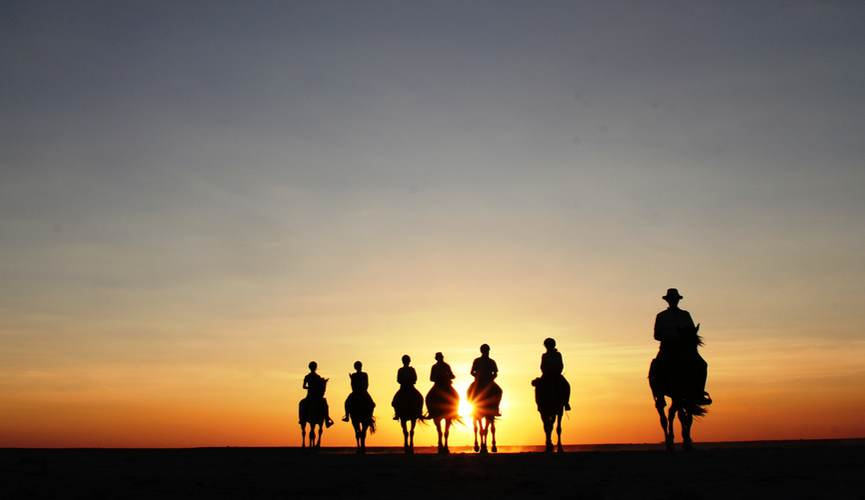 Horse riders in the Makgadikgadi sunset